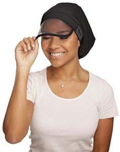 Black woman smiling, wearing hair bella cap